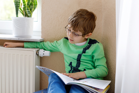 Little blonde school kid boy with glasses reading a book at home