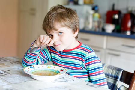 comedor escolar: Adorable little school boy eating vegetable soup indoor.