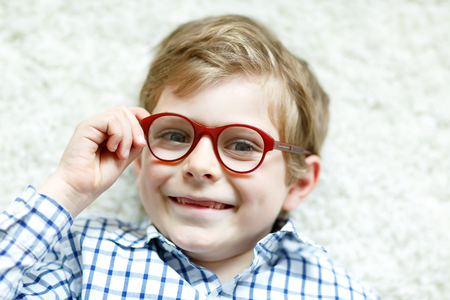 oculista: Close-up portrait of little blond kid boy with brown eyeglasses Foto de archivo
