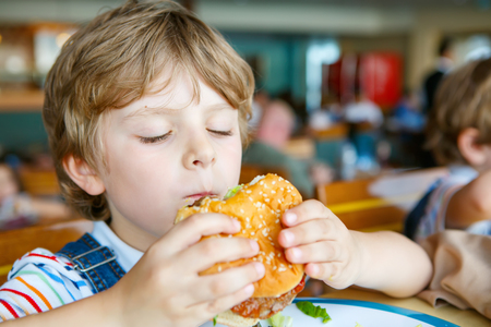 Cute healthy preschool boy eats hamburger sitting in school canteen Banco de Imagens