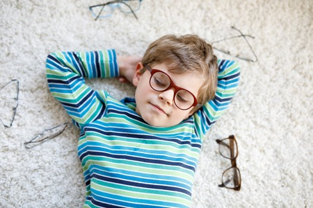 Close-up portrait of little blond kid boy with different eyeglasses on white background. Happy smiling child in casual clothes. Childhood, vision, eyewear, optician store. Boy choosing new glasses 写真素材