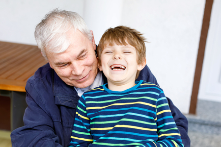Laughing grandfather with his grandson as they play together.