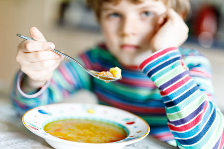 school cafeteria: Adorable little school boy eating vegetable soup indoor.
