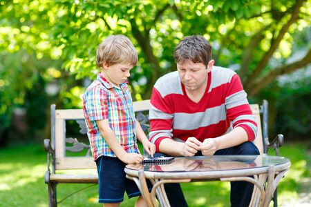 Little kid boy and father playing together checkers game