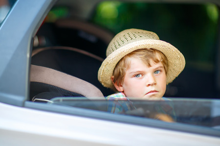 Sad tired kid boy sitting in car  during traffic jam Stock Photo
