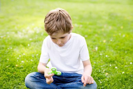 School kid playing with Tri Fidget Hand Spinner outdoors