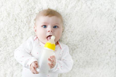 Nettes entzückendes ewborn Baby, das Krankenpflegeflasche hält und Formelmilch trinkt Standard-Bild - 80313255