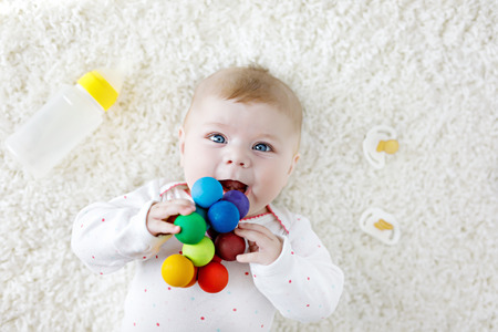 nursing bottle: Cute baby girl playing with colorful wooden rattle toy, nursing bottle and dummy Stock Photo