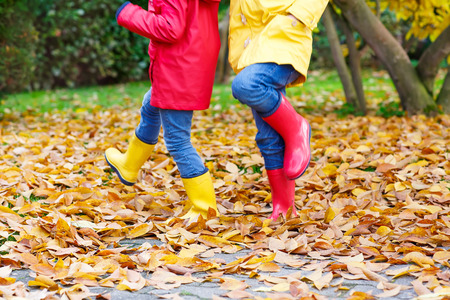 kiddies: Two little children playing in red and yellow rubber boots in autumn park