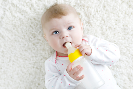 Cute adorable ewborn baby girl holding nursing bottle and drinking formula milk