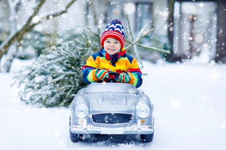 Grappige kleine lachende kind jongen rijden speelgoed auto met kerstboom.