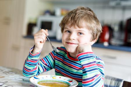 愛らしい小さな学校の男の子屋内の野菜スープを食べるします。