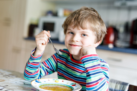 Adorable little school boy eating vegetable soup indoor.