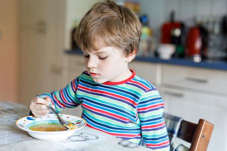comedor escolar: Pequeño muchacho adorable de la escuela que come la sopa vegetal dentro.