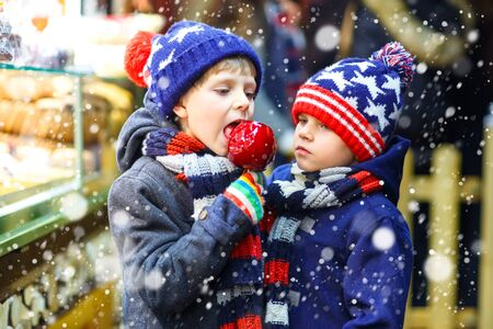 Two little kid boys eating sugar apple sweets stand on Christmas market