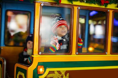 크리스마스 시장에서 회전 목마에 애들이 두 명있어. 스톡 콘텐츠