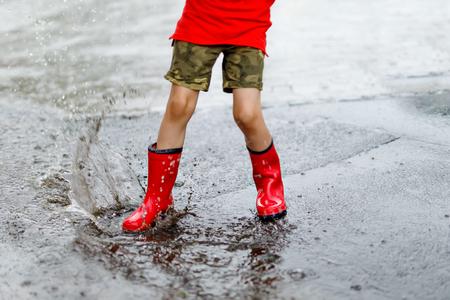 Kind dat rode regenlaarzen draagt die in een vulklei springen. Stockfoto