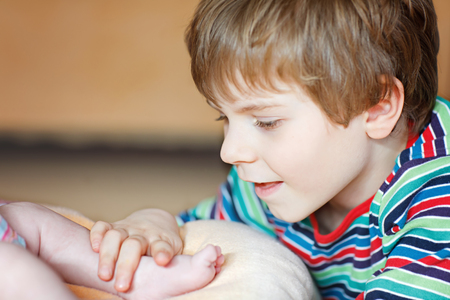 Little kid boy kissing and playing with foot of newborn baby.