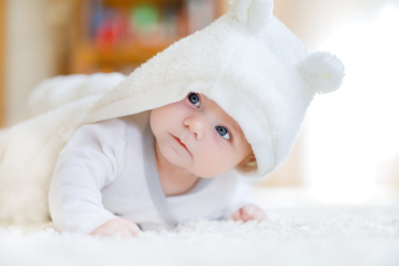 one sheet: Baby girl wearing white towel or winter overal in white sunny bedroom