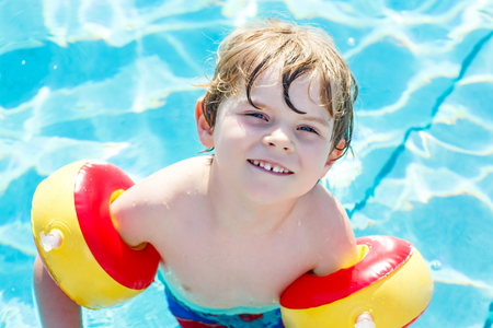 Happy little kid boy having fun in an swimming pool Stock Photo