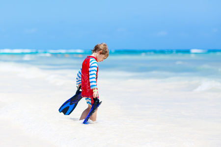 little blond kid boy having fun on tropical beach of Maldives