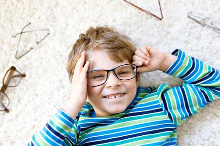 Close-up portrait of little blond kid boy with brown eyeglasses Imagens