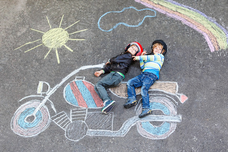Two kid boys in helmet with motorcycle picture drawing with colo Stock Photo