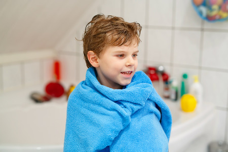 Happy little kid boy after taking bath with blue towel