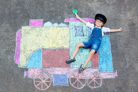 Niño pequeño que se divierte con las tizas del tren Foto de archivo - 81880077