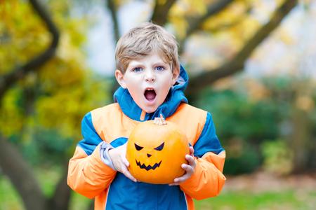 kiddies: happy cute little kid boy with halloween pumpkin lantern on autumn Stock Photo