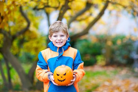 happy cute little kid boy with halloween pumpkin lantern on autumn Stock Photo