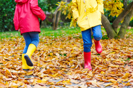 Two little children playing in red and yellow rubber boots in autumn park