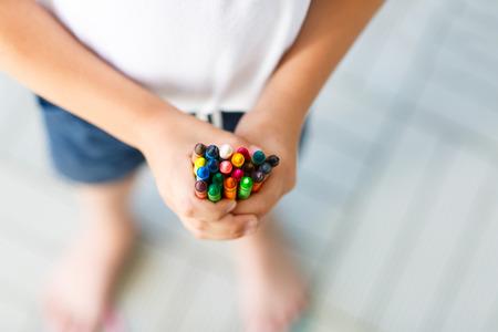 Close-up van de handen van het kind met veel kleurrijke waskleurpotloden potloden. Jong geitje die school en kinderdagverblijfmateriaal en studentenmateriaal voorbereiden. Terug naar school. Onderwijs, school, leerconcept. Stockfoto - 81942971
