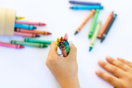 Close-up van de handen van het kind met veel kleurrijke potloden van waskleurpotloden. Jong geitje die school en kinderdagverblijfmateriaal en studentenmateriaal voorbereiden. Terug naar school. Onderwijs, school, leerconcept.
