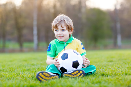 Little cute kid boy of 4 playing soccer with football on field, outdoors