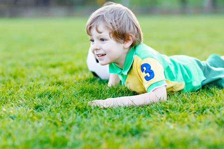 Piccolo ragazzo carino di 4 giocando a calcio con il calcio sul campo, all'aperto Archivio Fotografico - 81967546