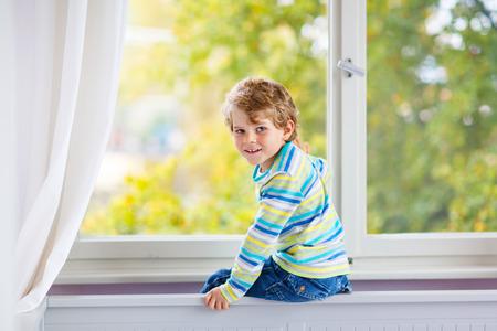 ittle: ittle kid boy sitting near window and looking on autumn trees