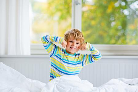 kidsroom: happy little kid boy after sleeping in bed in colorful nightwear Stock Photo