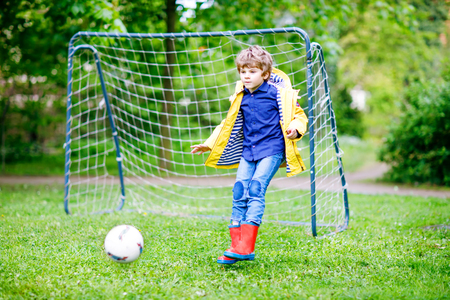aucasian: Active cute little kid boy playing soccer and football and having fun Stock Photo