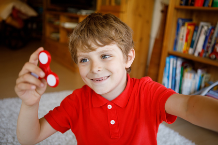 School kid playing with Tri Fidget Hand Spinner indoors