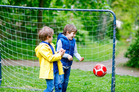 Two active kids boys playing soccer and football and having fun together