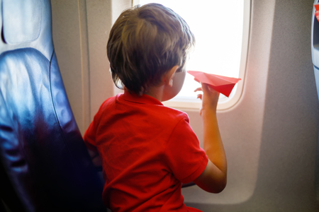 Little kid boy playing with red paper plane during flight on airplane Imagens