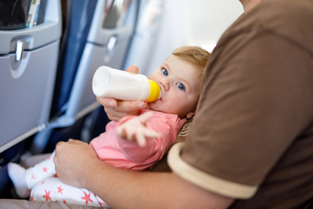 Dad holding his baby daughter during flight on airplane going on vacations 스톡 콘텐츠