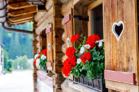 Typisch Beiers of Oostenrijks houten venster met rode geraniumbloemen op huis in Oostenrijk of Duitsland.