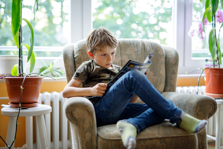 Cute blond little kid boy reading magazine in domestic room. Excited child reading loud, sitting on couch. Schoolkid, family, education.