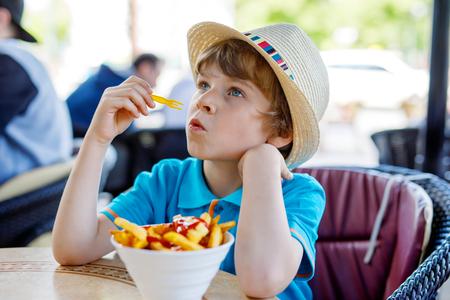Cute healthy preschool kid boy eats french fries potatoes with ketchup