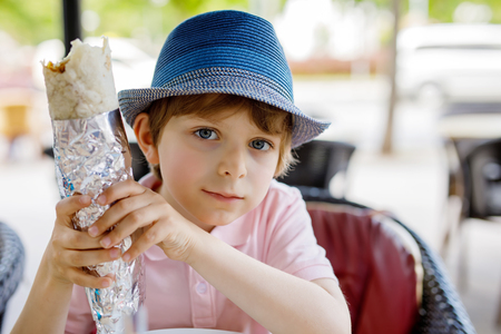 Cute healthy preschool kid boy eats turkish kebab sitting in cafe outdoors