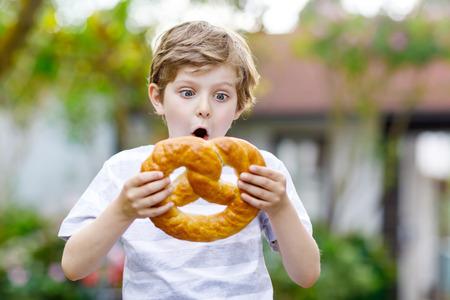 Adorable little kid boy eating huge big bavarian german pretzel. Фото со стока