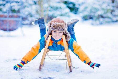 Little kid boy enjoying sleigh ride in winter