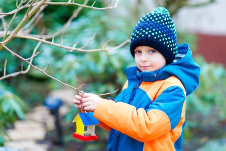 Little kid boy hanging bird house on tree for feeding in winter